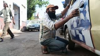 MUMBAI, INDIA - 10 JANUARY 2015: Indian men repainting a car on the street of Mumbai while people pass by.