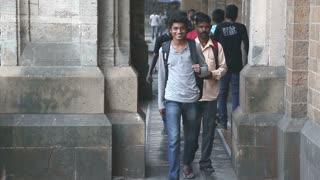 MUMBAI, INDIA - 10 JANUARY 2015: Indian teenage boys walking out of building.