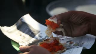 MUMBAI, INDIA - 10 JANUARY 2015: Man eating local food from newspaper in Mumbai, closeup.