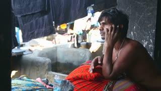 MUMBAI, INDIA - 10 JANUARY 2015: Man sitting and calling on the phone in a slum in Mumbai.