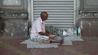 MUMBAI, INDIA - 10 JANUARY 2015: Man sitting on newspaper on the street and eating.
