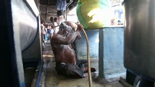 MUMBAI, INDIA - 10 JANUARY 2015: Man washing himself in a manufactory in slum of Mumbai.