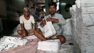 MUMBAI, INDIA - 10 JANUARY 2015: Men arranging white laundry in a laundry manufactory in Mumbai.