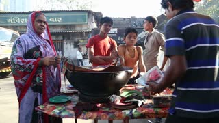 MUMBAI, INDIA - 10 JANUARY 2015: Men preparing and selling food in a street shop while local boys watch him.