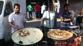 MUMBAI, INDIA - 10 JANUARY 2015: Men preparing and selling local food at a street stand in Mumbai.
