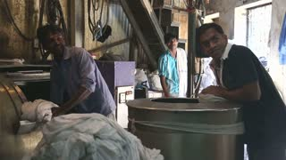 MUMBAI, INDIA - 10 JANUARY 2015: Men working in laundry manufactory in slum of Mumbai.