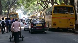 MUMBAI, INDIA - 10 JANUARY 2015: People and traffic on the street of Mumbai, back view.