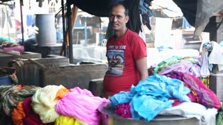 MUMBAI, INDIA - 10 JANUARY 2015: Portrait of Indian man behind a stand with clothes in Mumbai.