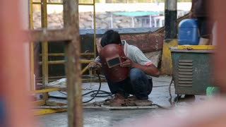 MUMBAI, INDIA - 10 JANUARY 2015: Worker with a protective mask welding in a workshop in Mumbai.