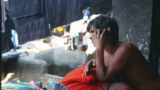 MUMBAI, INDIA - 10 JANUARY 2015: Worried man hanging up the phone in a slum in Mumbai.