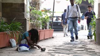 MUMBAI, INDIA - 10 JANUARY 2015: Young girl begging on the street of Mumbai while people pass by.