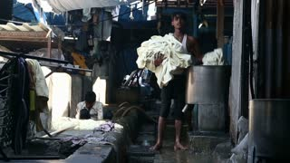 MUMBAI, INDIA - 10 JANUARY 2015: Young Indian man taking laundry from the canister in a manufactory in Mumbai.