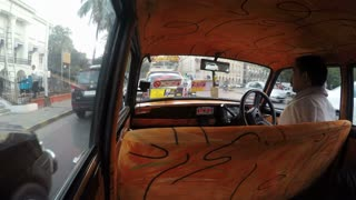 MUMBAI, INDIA - 11 JANUARY 2015: Back seat view of man driving taxi through busy street in Mumbai.