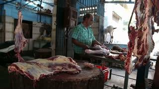 MUMBAI, INDIA - 11 JANUARY 2015: Indian man sharpening knife at a butchery in Mumbai.