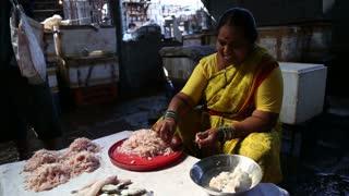 MUMBAI, INDIA - 11 JANUARY 2015: Indian woman cleaning shrimps at a market stand in Mumbai.