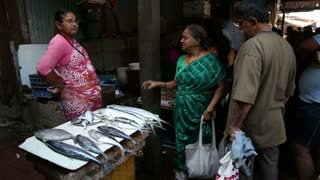 MUMBAI, INDIA - 11 JANUARY 2015: Indian woman talking at a fish stand of market in Mumbai.
