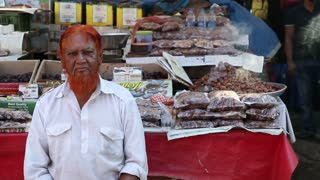 MUMBAI, INDIA - 11 JANUARY 2015: Man with orange hair sitting in front of a street stand in Mumbai.
