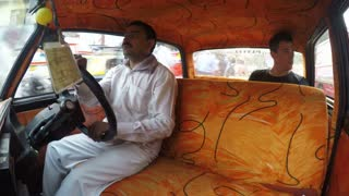 MUMBAI, INDIA - 11 JANUARY 2015: Young European man driving in taxi with Indian taxi driver, timelapse.
