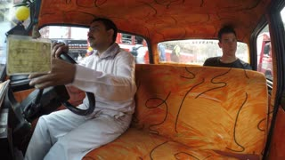 MUMBAI, INDIA - 11 JANUARY 2015: Young European man driving in taxi with Indian taxi driver.