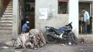 MUMBAI, INDIA - 12 JANUARY 2015: Animal skin on pile and motorcycle in front of a house in Mumbai.