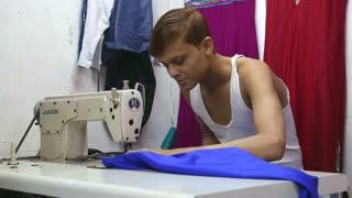 MUMBAI, INDIA - 12 JANUARY 2015: Boy sewing clothes on a machine in Mumbai.