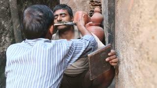 MUMBAI, INDIA - 12 JANUARY 2015: Indian man cutting moustache in a narrow street in Mumbai.