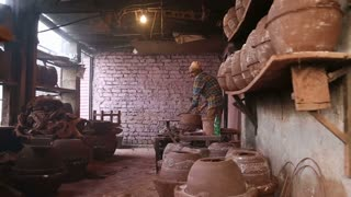 MUMBAI, INDIA - 12 JANUARY 2015: Indian man making a bowl out of clay in workshop in Mumbai.