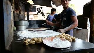 MUMBAI, INDIA - 12 JANUARY 2015: Indian man preparing dough for naan in workshop in Mumbai.