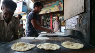 MUMBAI, INDIA - 12 JANUARY 2015: Indian man preparing naan on grill in workshop in Mumbai.