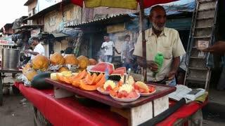 MUMBAI, INDIA - 12 JANUARY 2015: Man selling local fruits at street stand in Mumbai.