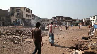 MUMBAI, INDIA - 12 JANUARY 2015: People passing through a dirty street in Mumbai, with buildings in background.