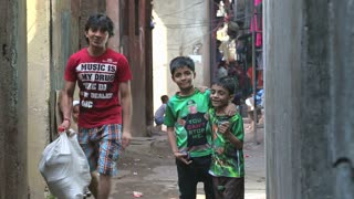 MUMBAI, INDIA - 12 JANUARY 2015: Portrait of children in a narrow street in Mumbai while people pass.