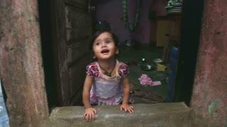 MUMBAI, INDIA - 12 JANUARY 2015: Portrait of Indian baby girl looking through the window.