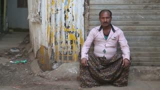 MUMBAI, INDIA - 12 JANUARY 2015: Portrait of Indian man sitting on the street in Mumbai.