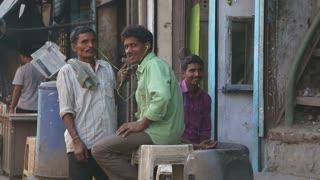 MUMBAI, INDIA - 12 JANUARY 2015: Portrait of three man sitting at street in Mumbai, closeup.