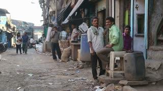 MUMBAI, INDIA - 12 JANUARY 2015: Portrait of three man sitting at street in Mumbai, with people passing by.