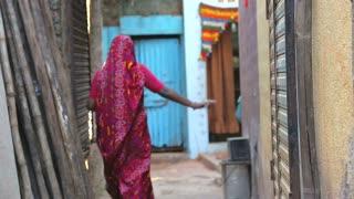 MUMBAI, INDIA - 12 JANUARY 2015: Woman passing through a narrow street in Mumbai.