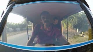 MUMBAI, INDIA - 13 JANUARY 2015: Indian man driving young European man through countryside.