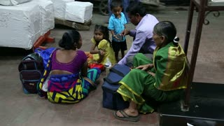 MUMBAI, INDIA - 14 JANUARY 2015: Family sitting and waiting on the floor of train station in Mumbai.