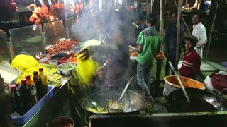 MUMBAI, INDIA - 14 JANUARY 2015: Indian man preparing local food at a street stand in night in Mumbai.