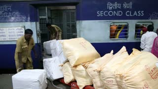 MUMBAI, INDIA - 14 JANUARY 2015: Workers loading packages into train at train station in Mumbai.