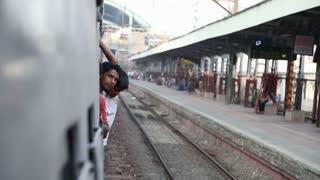 MUMBAI, INDIA - 16 JANUARY 2015: Indian man looking peeking out the window during a train ride.