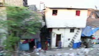 MUMBAI, INDIA - 16 JANUARY 2015: View on street full of garbage during a train ride in Mumbai.