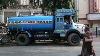 MUMBAI, INDIA - 17 JANUARY 2015: Blue water tank truck at the street in Mumbai, with people passing.