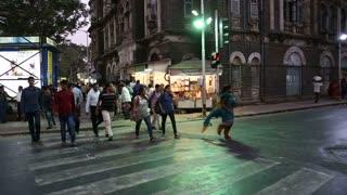 MUMBAI, INDIA - 17 JANUARY 2015: People crossing crossroads at a street in Mumbai at sunset.