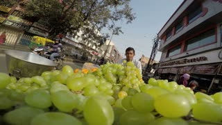 MUMBAI, INDIA - 3 FEBRUARY 2015: Man transporting pile of grapes down the road, closeup.