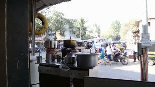 MUMBAI, INDIA - 7 JANUARY 2015: Equipment for chai preparation, with busy street in the background.