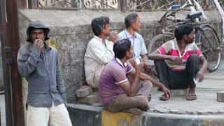 MUMBAI, INDIA - 7 JANUARY 2015: Local Indian men sitting and talking on the street of Mumbai.