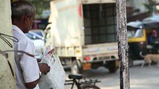 MUMBAI, INDIA - 7 JANUARY 2015: Local man reading newspapers on a busy street of Mumbai.