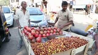 MUMBAI, INDIA - 7 JANUARY 2015: Local vendors selling pomegranate on a street of Mumbai.